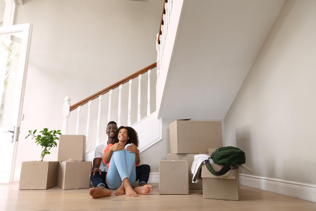 Front view of an African American couple at home, moving in, sitting on the floor embracing next to cardboard boxes. Family enjoying time at home, lifestyle concept